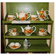 Un mobile di color verde con delle tazze e servizio del tè' con disegni di fiori