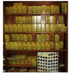 Un mobile alto con tante mensole e dei prodotti in confezioni gialle e degli esempi per tinta dei capelli