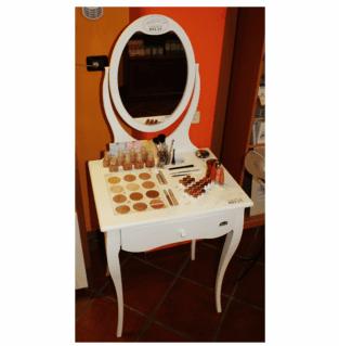 Un tavolino bianco con specchio e sopra dei cosmetici e trucchi esposti
