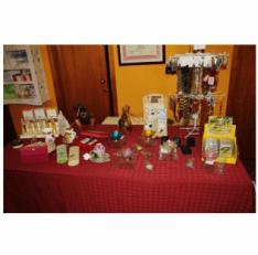Un tavolo con tovaglia rossa con dei oggetti e prodotti esposte