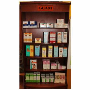 Un mobile marrone con mensole con dei prodotti e sul mobile scritta Guam