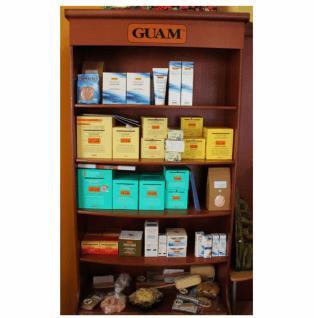 un mobile marrone con mensole con dei prodotti e sul mobile scritta Guam su uno sfondo bianco