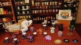 Un tavola con esposizione di un servizio del tè' e un cestino di paglia sulla sinistra