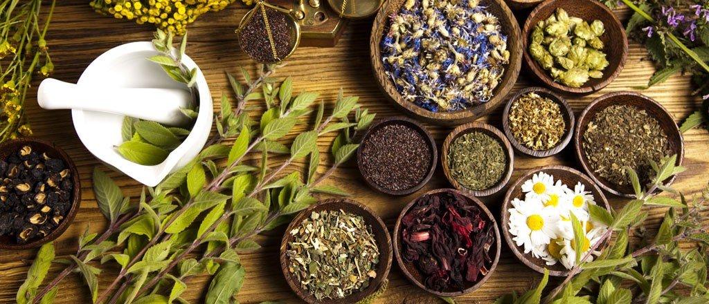 Erbe, fiori e spezie in ciotole su un tavolo di legno