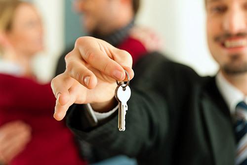 Insurance broker handing the keys to customer for their insurance needs in Thomaston, GA