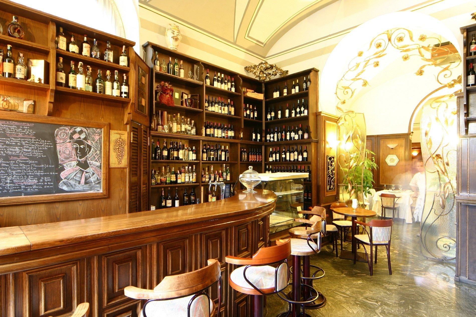 Immagine del pub rivestito di legno, sgabelli alti e decorato come un pub britannico