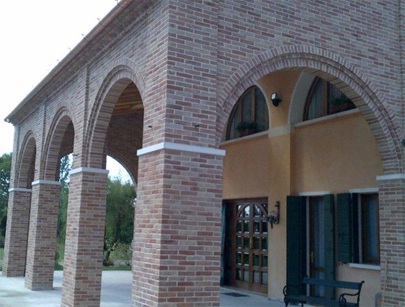 una costruzione a colonne con mattoni a vista con sotto un patio