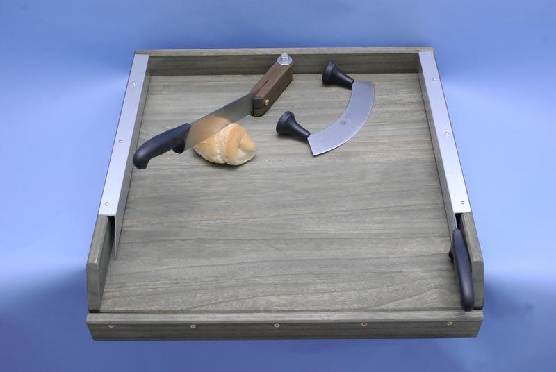 tagliere con diversi tipi di coltelli e un pezzo di pane-vista laterale