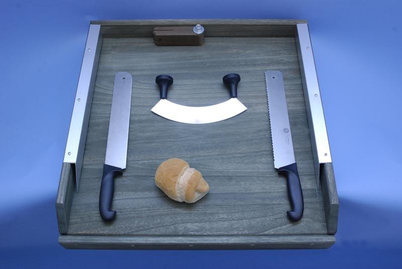 tagliere con diversi tipi di coltelli e un pezzo di pane-vista frontale