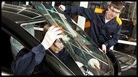 Due carrozzieri sostituiscono il parabrezza di un'auto