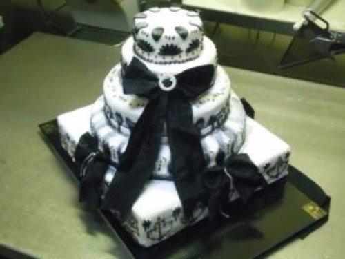 Originale torta di cinque piani di crema e decorata con un laccio nero