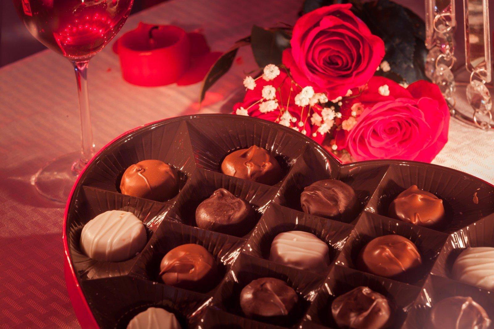 Cassa in forma di cuore con cioccolatini, rose rosse e la coppa di vino