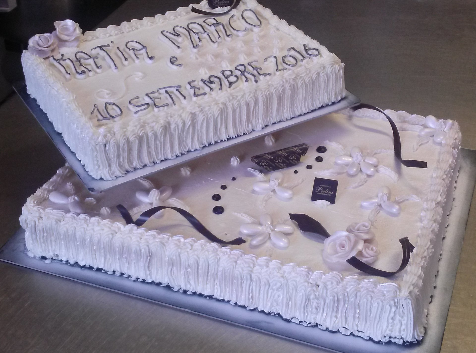 Originale torta nuziale rettangolare di due piani di crema e dettagli di cioccolato