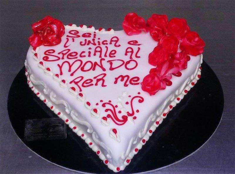 Torta di compleanno con sei piccole torte di crema e un grande cuore azzurro