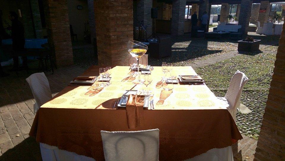 Tavolino esterno con bicchiere di vino bianco