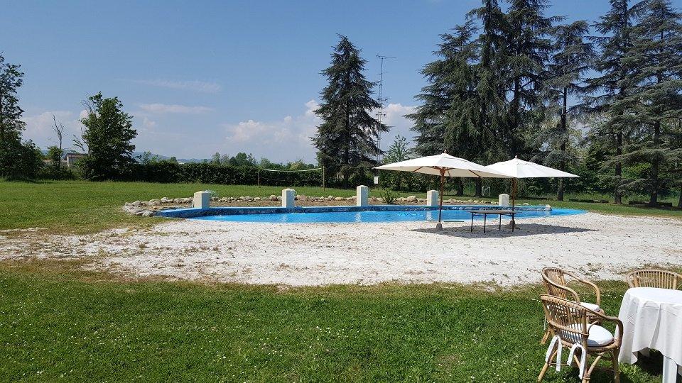 Area verde con piscina e ombrelloni