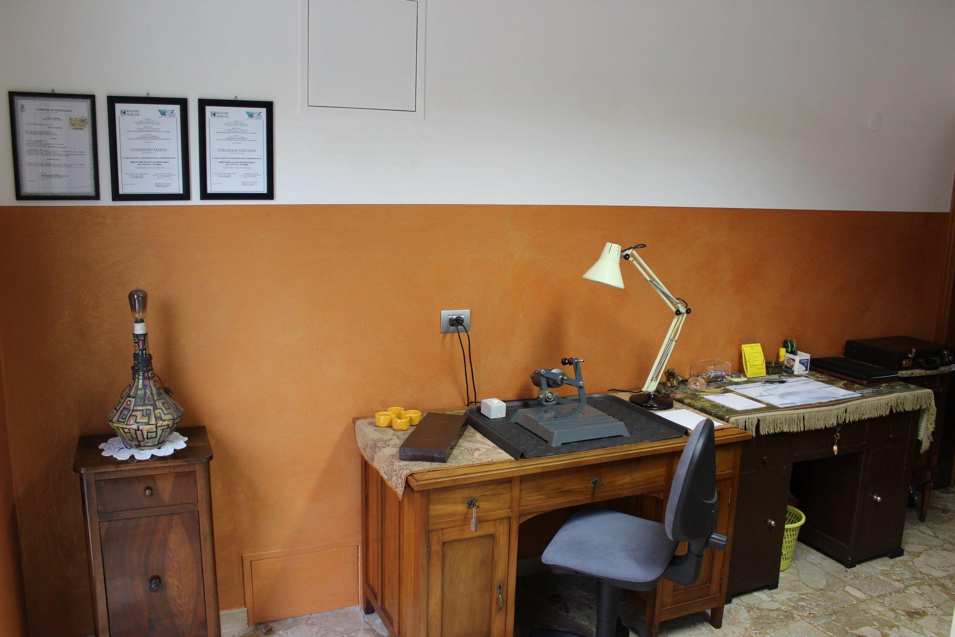 una scrivania con una sedia all'interno dell'ufficio dell'impresa funebre