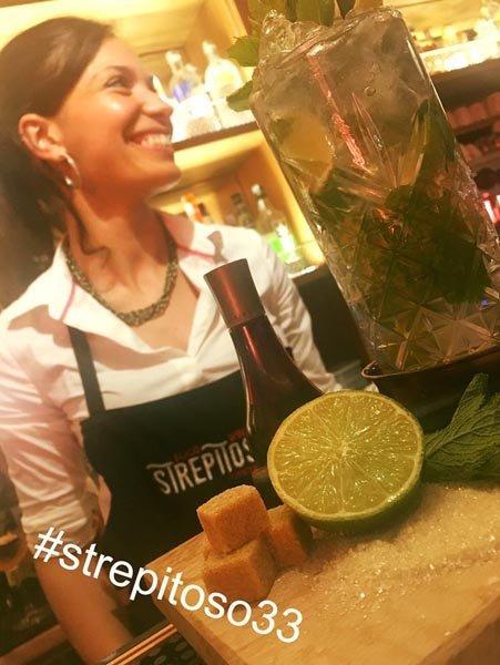 barista di profilo sorride davanti a un cocktail