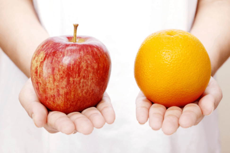 Person holds out an apple in one hand and an orange in the other.