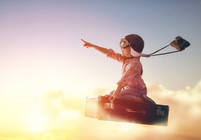 A child dressed like a pilot with a camera rides a briefcase in the clouds and points forward.