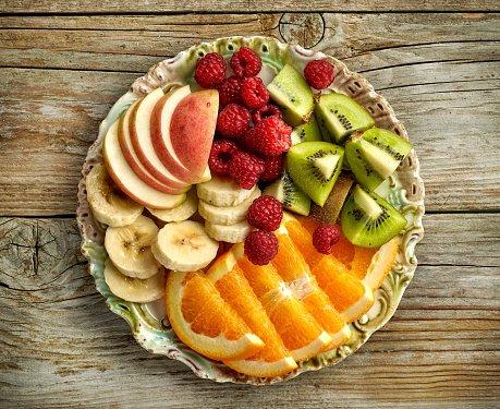Wooden plate of sliced apples, oranges, bananas, strawberries, and kiwis.