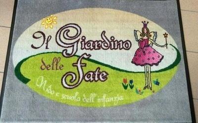 un tappeto con un disegno e la scritta Il giardino delle fate