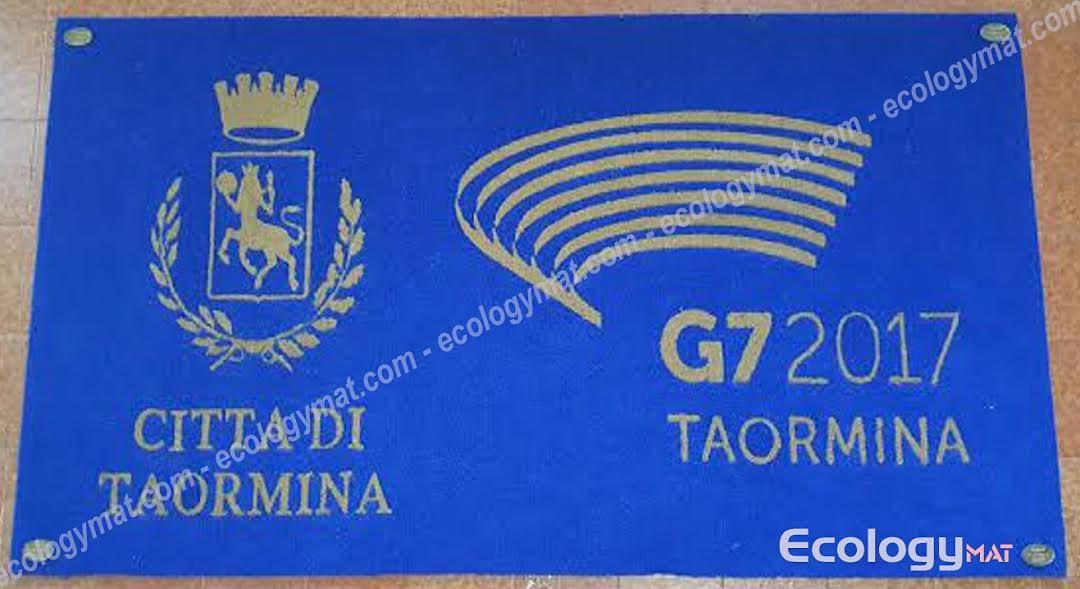 un tappeto blu con scritto città di Taormina G7 2017