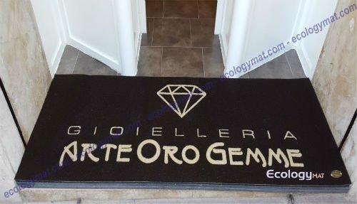 uno zerbino nero con scritto gioielleria arte oro gemme e il disegno di un diamante