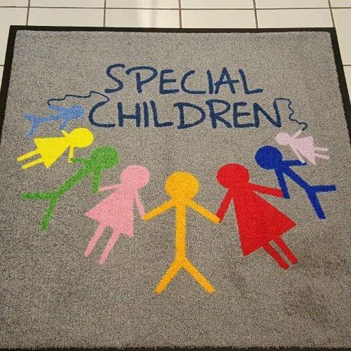 un tappeto grigio con scritto Special Children e degli omini colorati