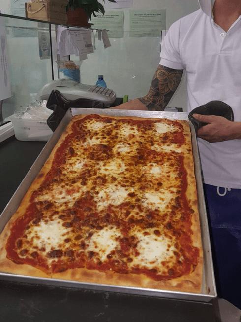 La pizzeria prepara fantastiche pizze in teglia, ideali per buffet.