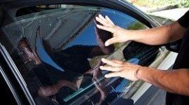 vetro auto oscurato, mani del carrozziere che applica pellicola oscurante, auto scura