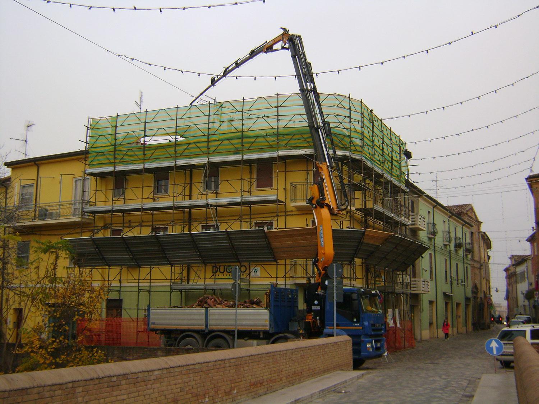 un camion e un'impalcatura davanti a un edificio giallo