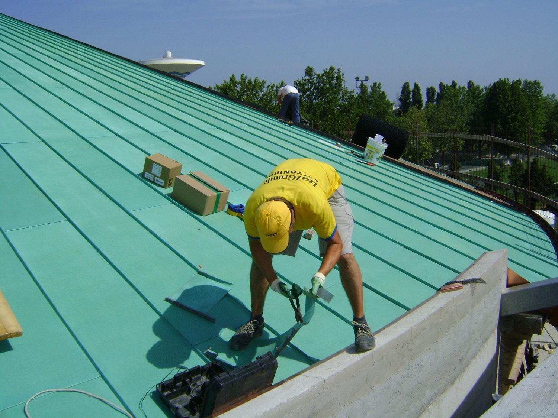 Un uomo chinato in avanti al lavoro su un tetto