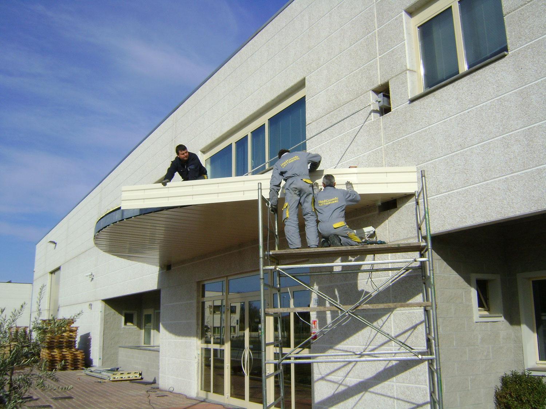 Due uomini su ponteggio al lavoro su tettoia