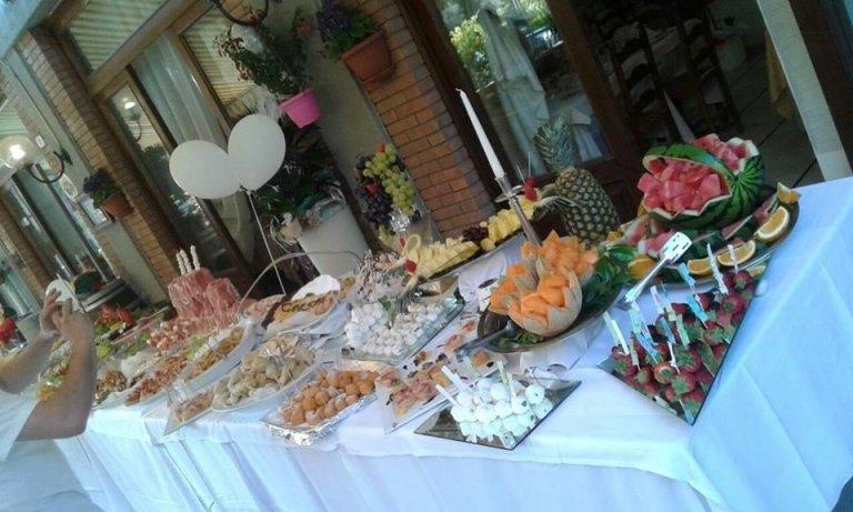 Grande tavola buffet con snack salati in un lato e frutta e dolce nell'altro
