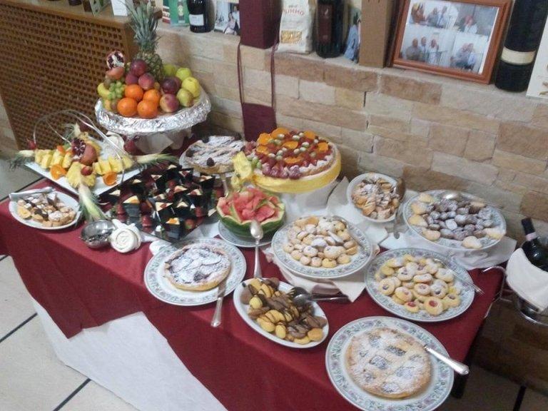 Tavola di dessert dove vediamo varie torte fatte con frutta, della pasticceria surtida,paste dolci e frutta tagliate