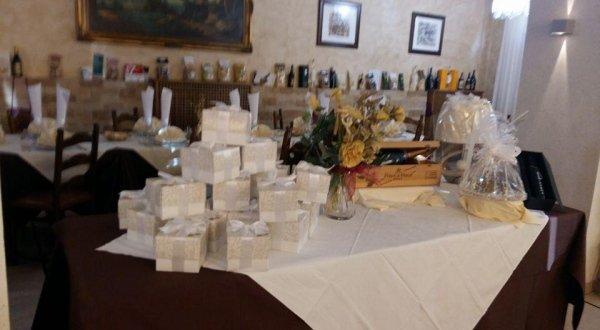 Vista del ristorante dove vi è una tavola piena di regali per una conclusione