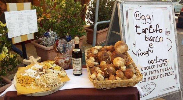 Cartello annunciando il piatto del giorno e al lato una tavola con tutti gli ingredienti