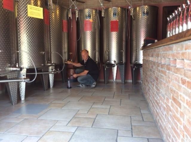 un uomo che spilla del vino dai fermentatori