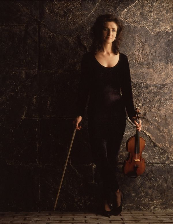 madeleine holding a violin with stone background