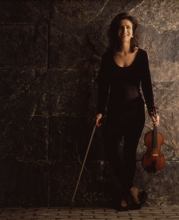 madeleine mitchell holding a violin with stone background