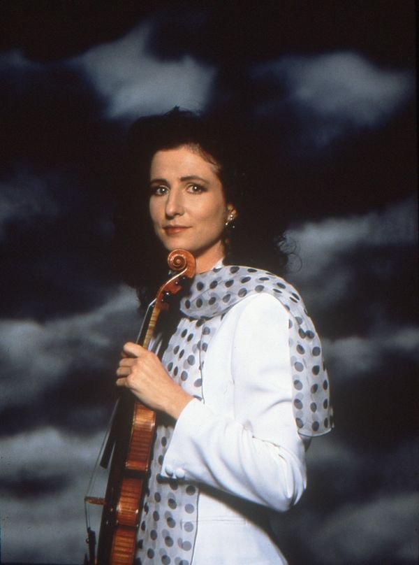 madeleine mitchell holding a violin on clouds background