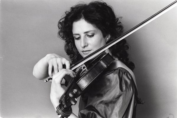 young madeleine mitchell playing violin on black and white background