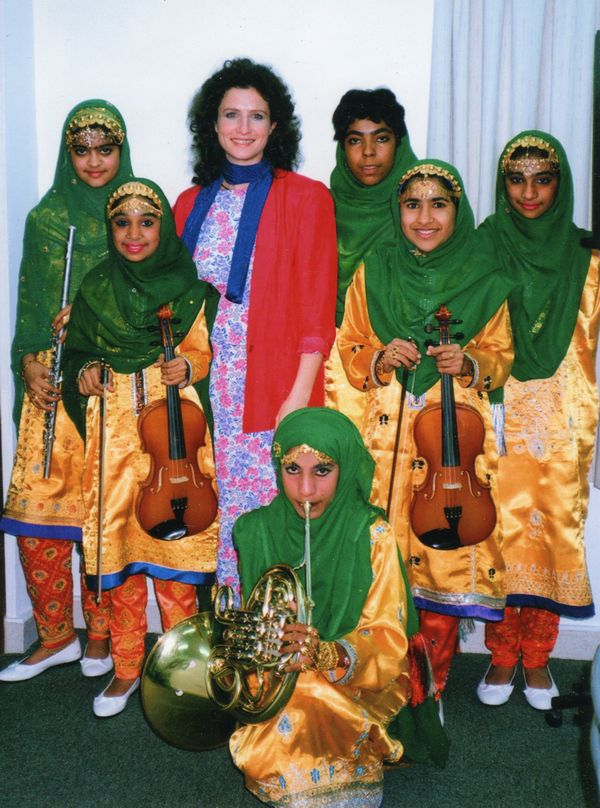 madeleine mitchell surrounded by children with green scarves