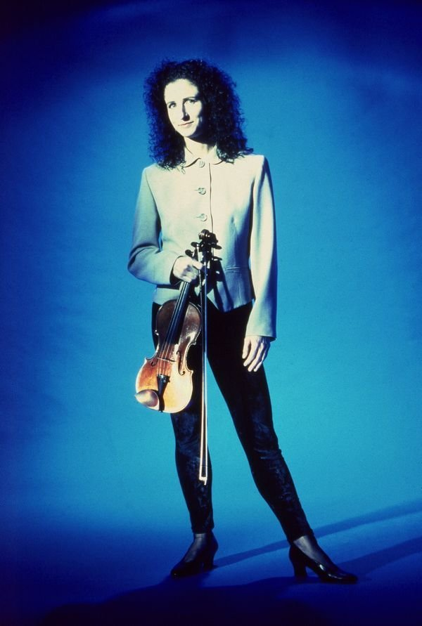 madeleine mitchell holding a violin on electric blue background