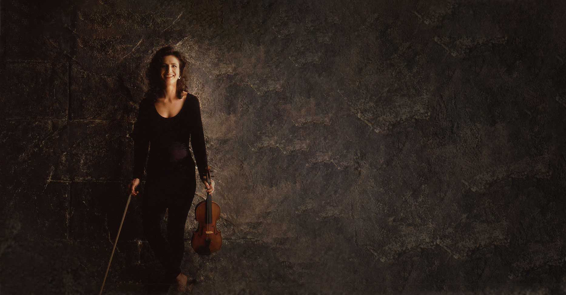 madeleine mitchell against a stone wall background and holding a violin
