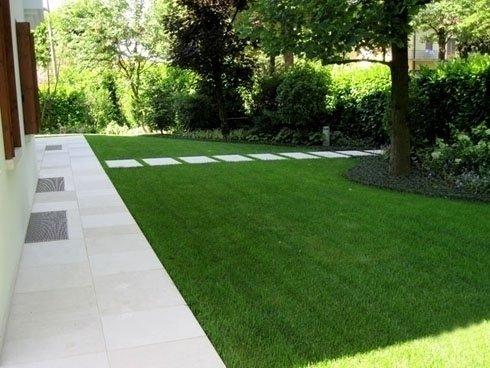 prato verde con sentiero di mattonelle chiare sullo sfondo