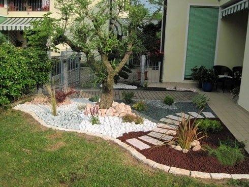 due aiuole con piante ed albero divise da sentiero di mattonelle
