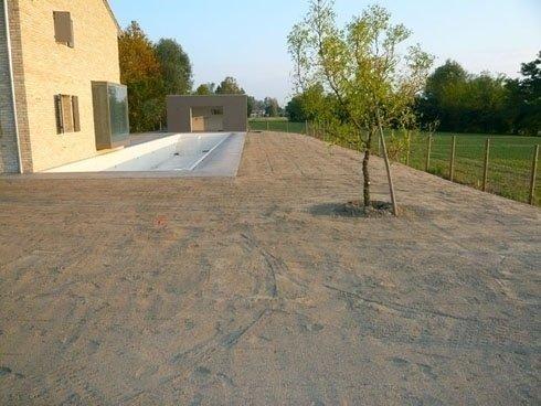 terreno con albero, casa e pscina sullo sfondo