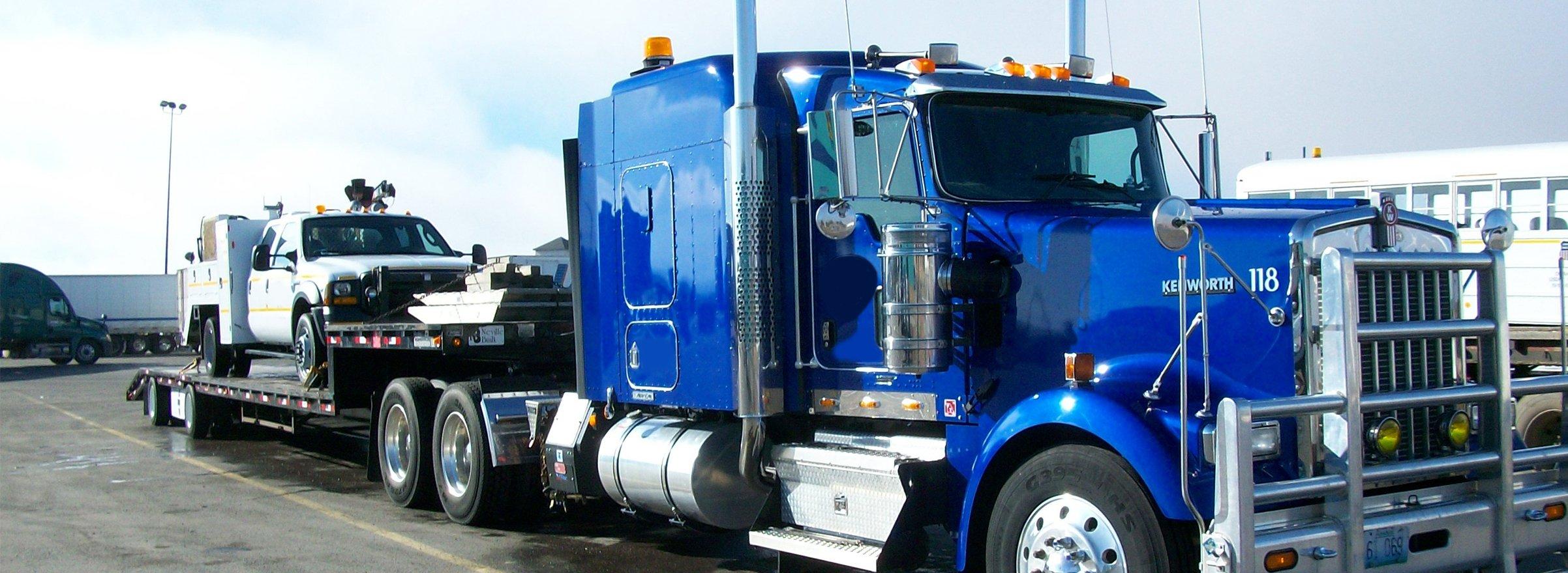 Blue semi hauling a broke down electrical truck
